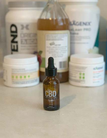 CBD Oil Tincture in amber bottle in front of other supplements